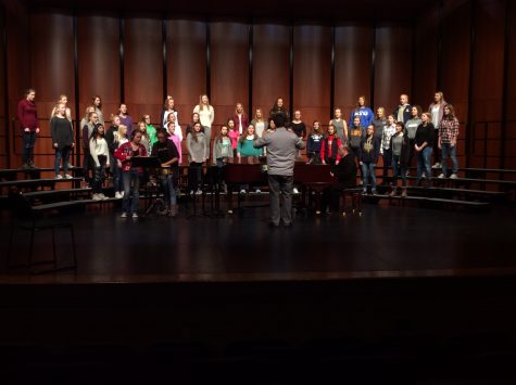 The Choralaires practice on stage under the direction of choir director Mr. Robert Hahn.